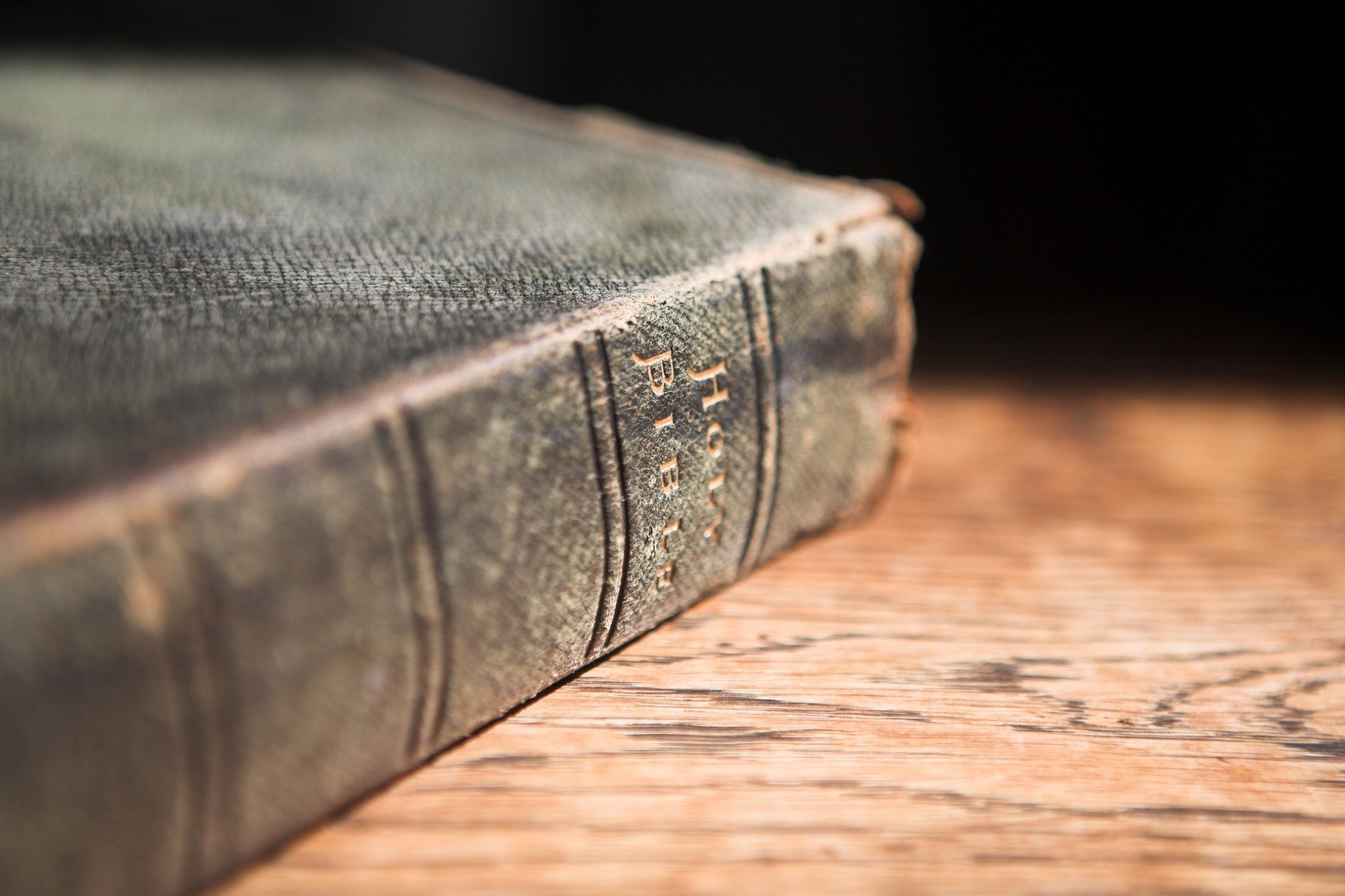 Leather covered old bible lying on a wooden table in a beam of sunlight (not an isolated image) VERY SHALLOW Depth of field  Focus on Text Holy Bible